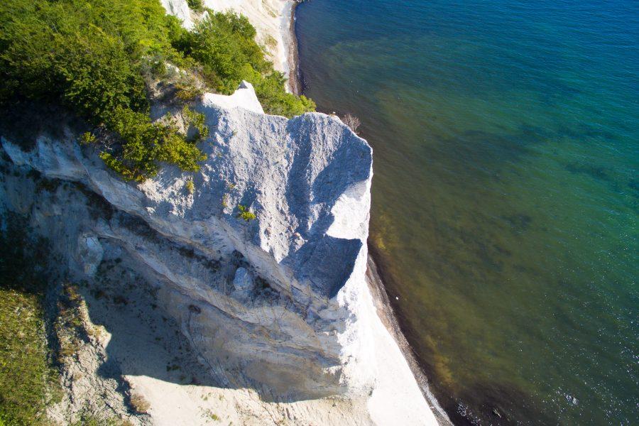 De klippelignende hvide klinter ligger smukt ud til havet, der tæt på stranden er farvet matgrønt af kridt i opløsning. Foto: Thomas Ix